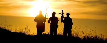 Three fighters, seen as shadows, holding weapons in the sunset.
