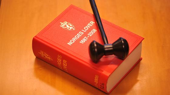 A gavel on a red, Norwegian collection of laws