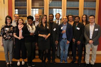 Picture of the presenters at the colloquium, standing in front of a bookshelf.
