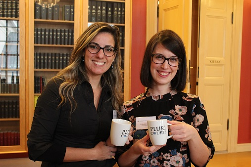 Picture of Katherine Quinn and Marcia Alvarenga holding the PluriCourts mugs they won for outstanding presentations.