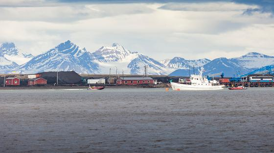 Image from Svalbard showing ocean, houses, and mountains
