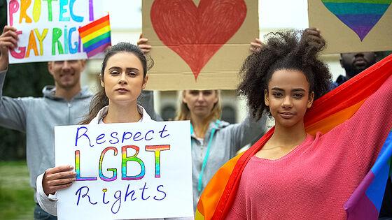 """Pride-parade. To personer står foran en gruppe som holder regnbueflagg og plakater. Personen til venstreholder en plakat hvor det står """"respect LGBT rights"""". Personen til høyre holder et stort regnbueflagg."""